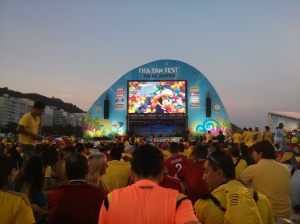 Fans without tickets watch the match on a video screen.