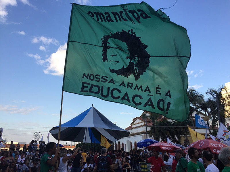 "A flag from the popular education movement Emancipa states, ""Education is our weapon!"" It depicts the face of Marielle Franco, a city councilwoman and former popular educator in Rio de Janeiro assassinated in 2018. (Photo by Alice Taylor.)"