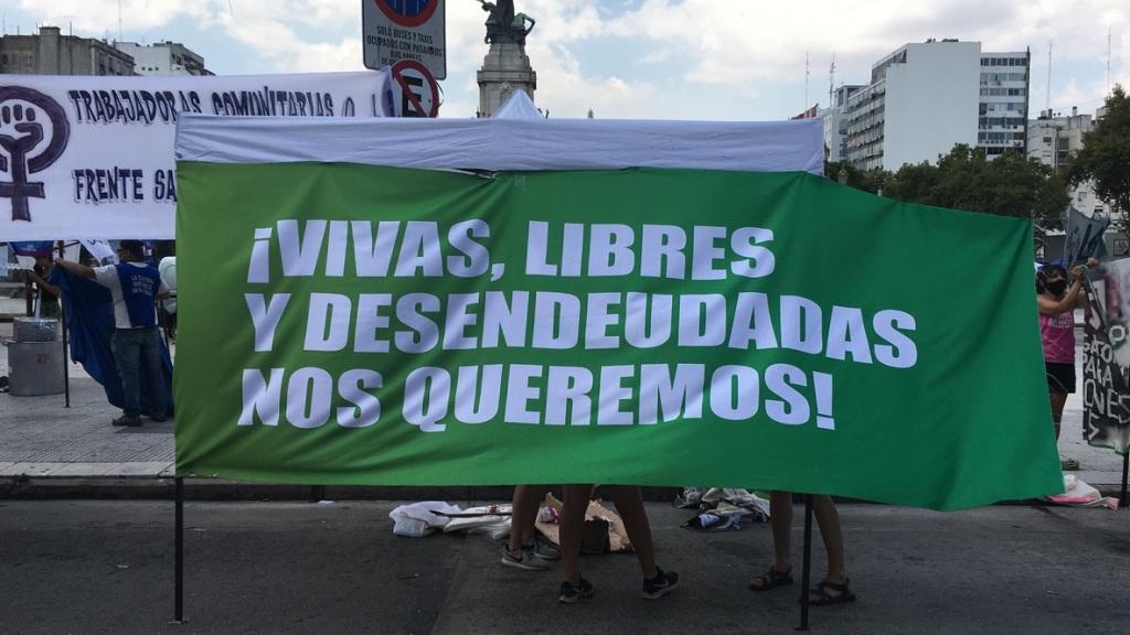 """Foto de la manifestación por el 8 de marzo en Buenos Aires, 2021. Un grupo de manifestantes muestra una gran bandera verde que dice """"¡Vivas, libres y desendeudadas nos queremos!"""". (Foto de Sofia Besandon.)"""